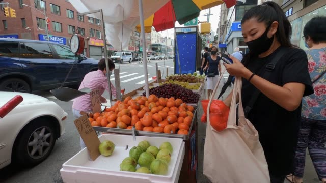stockvideo's en b-roll-footage met woman wearing a protective mask purchases fruit from a street vendor in manhattan's chinatown as the city continues phase 4 of re-opening following... - straatverkoper