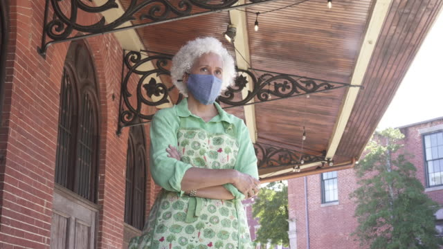 woman wearing a protective mask standing in front of business - street name sign stock videos & royalty-free footage