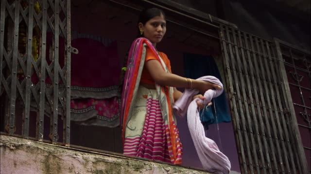 a woman wearing a sari wrings water from a wet towel. available in hd. - sari stock videos and b-roll footage