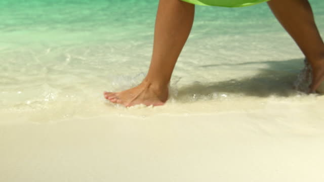 A woman wearing a sarong walks on the beach at a tropical island resort hotel. - Slow Motion