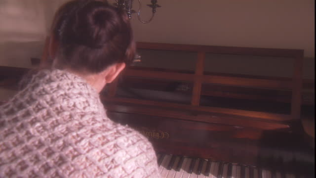 A woman wearing a shawl plays a piano.