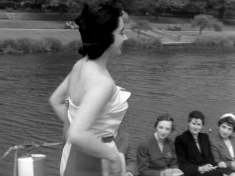 woman wearing a strapless top and trousers models on the deck of a boat on the river thames. 1953. - strapless stock videos & royalty-free footage