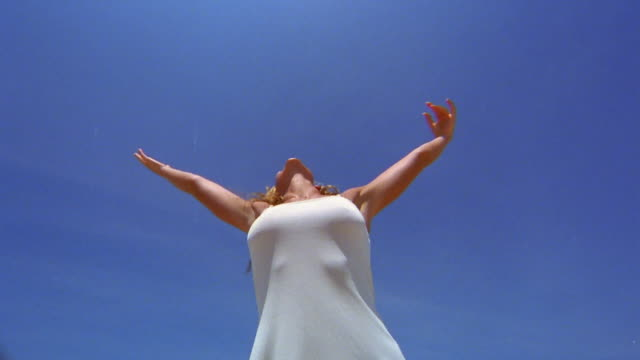 A woman wearing a white dress stretches her arms toward the sky.