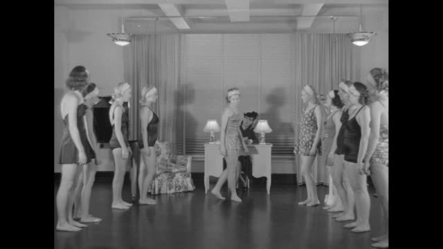 vídeos de stock, filmes e b-roll de woman wearing bathing suit walking with small block on head instructor anne delafield assisting her other women watching / women standing in two rows... - estudante universitária