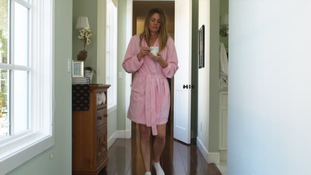 MS Woman wearing bathrobe drinking tea standing in hallway, Phoenix, Arizona, USA