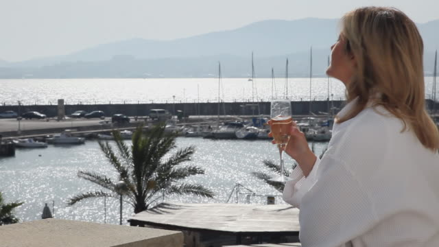 MS Woman wearing bathrobe standing in hotel room balcony, drinking champagne / Palma de Mallorca, Mallorca, Baleares, Spain