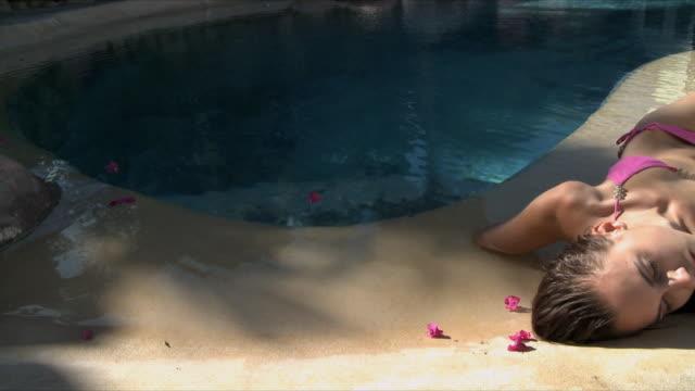 ms pan woman wearing bikini lying on poolside / cape town, south africa - 美しい女性点の映像素材/bロール