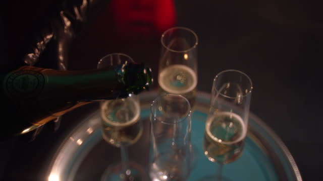 cu slow mo woman wearing black gloves pours chamapgne into tall glasses on a tray - 盆点の映像素材/bロール