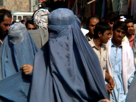 MS Woman wearing burka and people walking at fair, Kabul City, Kabul, Afghanistan