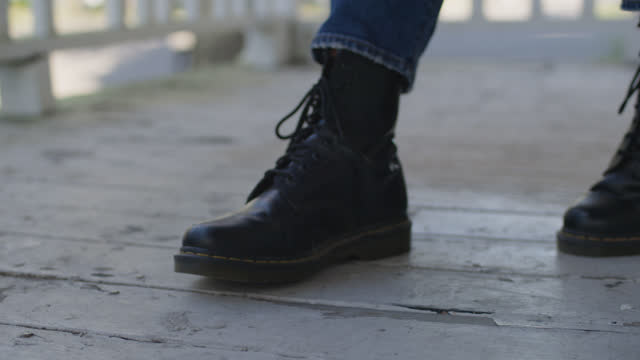 cu woman wearing combat boots taps foot lightly on porch floor - tapping stock videos & royalty-free footage