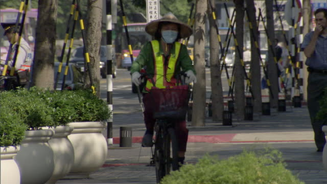 ms pan woman wearing conical straw hat and reflective vest riding bicycle and busy city street / taipei, taipei county, taiwan - insel taiwan stock-videos und b-roll-filmmaterial