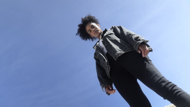 woman wearing denim jacket against blue sky, low angle - jeans bildbanksvideor och videomaterial från bakom kulisserna