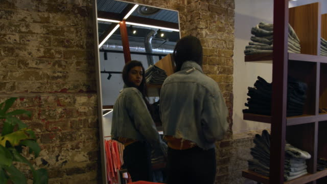vídeos de stock e filmes b-roll de woman wearing denim jacket - cabine de loja