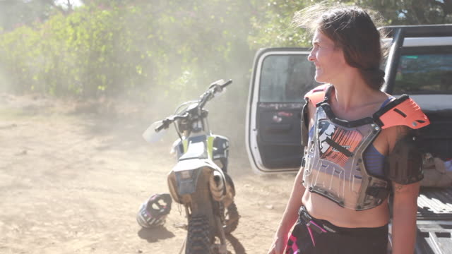 a woman wearing dirt bike gear watching young boys riding around the dirt bike track - kelly mason videos stock videos & royalty-free footage