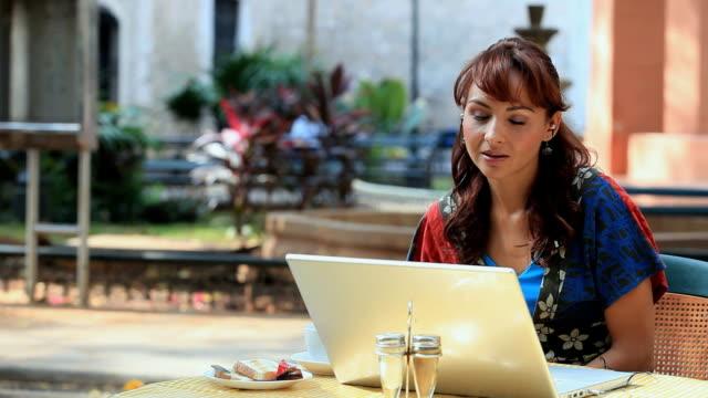 vídeos y material grabado en eventos de stock de ms woman wearing earpiece talking on phone while looks at laptop, merida, yucatan, mexico - mérida méxico