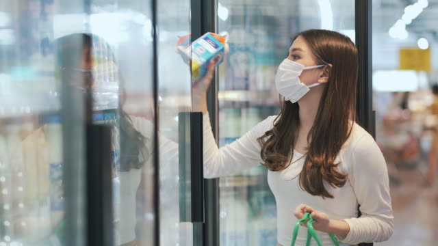woman wearing face mask shopping freezer product in supermarket - dairy product stock videos & royalty-free footage