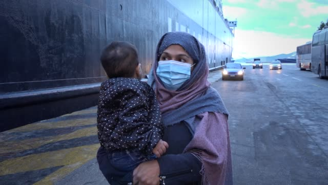 woman wearing face mask to prevent the spread of the coronavirus, holds her child, as migrants from the moria camp in lesbos island, wait for a bus... - refugee camp stock videos & royalty-free footage