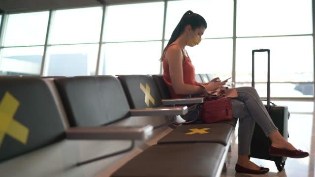 vídeos de stock, filmes e b-roll de mulher usando máscara facial usando smartphone em área de espera do aeroporto - turismo urbano