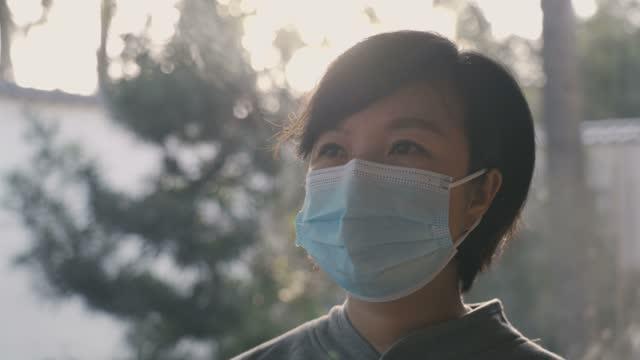 vídeos y material grabado en eventos de stock de mujer usando máscara facial - epidemiología