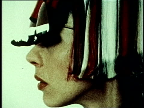 woman wearing far out fashions including a funny hat, colored wig and fake eyelids / different words for synthetic fabrics appear on screen bizarre... - 1971年点の映像素材/bロール