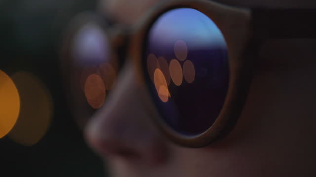 Woman wearing fashionable eyewear. Lights reflecting in glasses