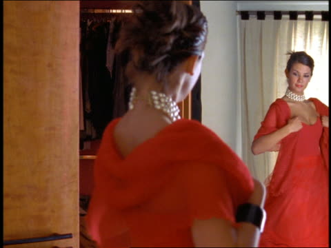 ms woman wearing formal red dress turning + looking at reflection in mirror - red dress stock videos & royalty-free footage