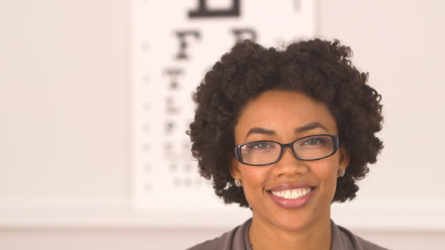 vídeos de stock, filmes e b-roll de woman wearing glasses at optometrist - só uma mulher de idade mediana
