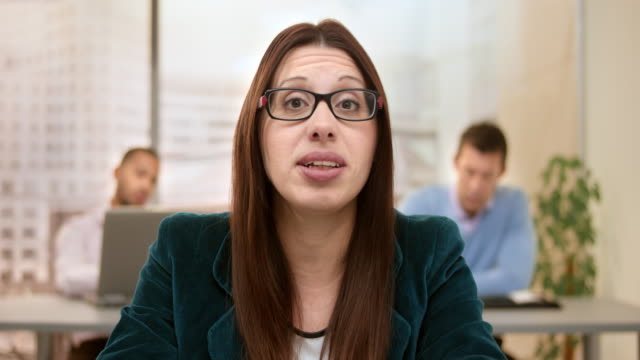 woman wearing glasses making a video call from the office - voip stock videos & royalty-free footage