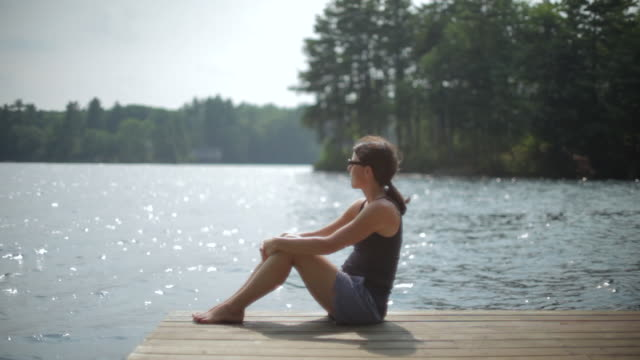 MS Woman wearing glasses sitting on dock and looking out / WOLFEBRO, NH, USA