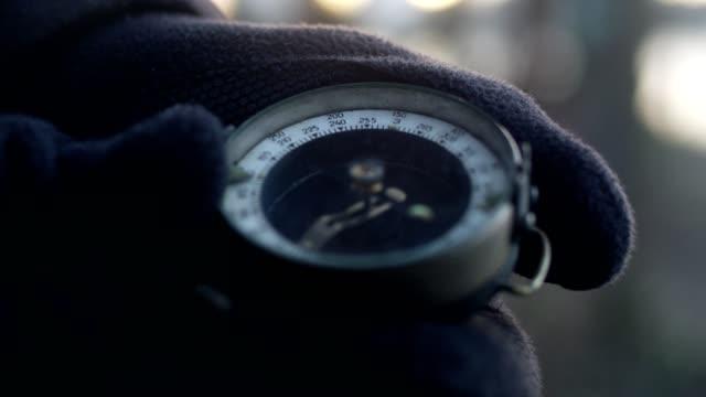 frau mit handschuhen kompass hält. reiseplanung - kompass stock-videos und b-roll-filmmaterial