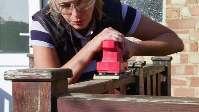 vidéos et rushes de woman wearing goggles uses a power sander - terrasse
