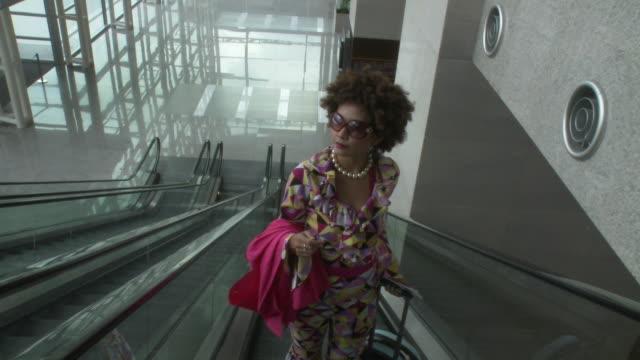 vídeos de stock e filmes b-roll de ms ha pov woman wearing groovy clothes standing on escalator moving up / bangkok, thailand - camisa com folhos