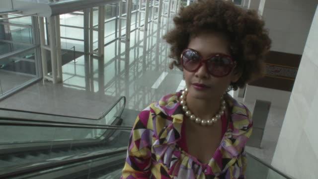 vídeos de stock e filmes b-roll de cu ha pov woman wearing groovy clothes standing on escalator moving up / bangkok, thailand - camisa com folhos
