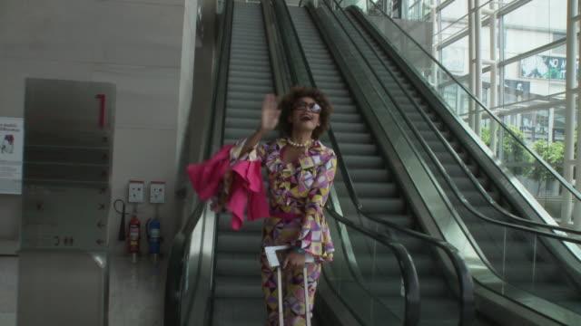 MS Woman wearing groovy clothes waving and kissing goodbye, taking escalator in lobby / Bangkok, Thailand