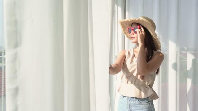 vídeos de stock, filmes e b-roll de mulher usando chapéu e óculos de sol abrindo a cortina da janela no quarto de hotel - chapéu