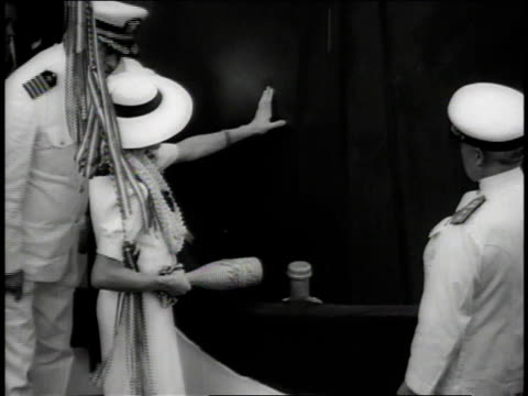 1937 ms woman wearing hat inspects side of ship, then smashes bottle on it, christening the ship as the captain looks on and applauds, the broken bottle is lifted away by a cord / new york city, new york, united states - flasche stock-videos und b-roll-filmmaterial