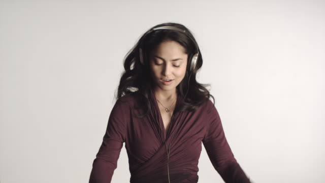 MS Woman wearing headphones dancing, studio shot / Los Angeles, California, USA