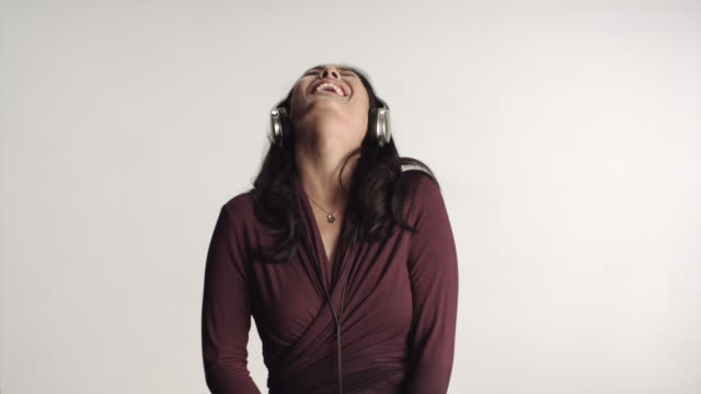 vídeos de stock e filmes b-roll de ms woman wearing headphones laughing, shaking head, studio shot / los angeles, california, usa - bater com a cabeça
