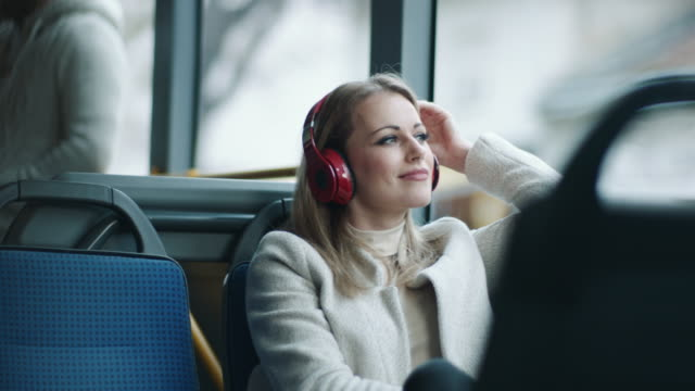woman wearing headphones on head on the bus - commuter stock videos & royalty-free footage