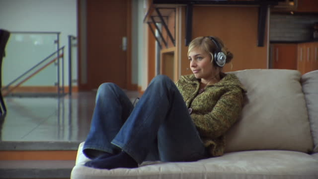 slo mo ws ds woman wearing headphones sitting on sofa, listening music / whistler, british columbia, canada - pullover stock videos & royalty-free footage