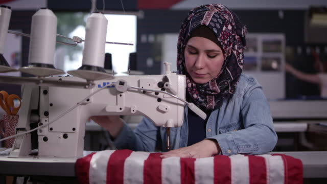 stockvideo's en b-roll-footage met woman wearing headscarf sewing american flag - made in the usa korte frase