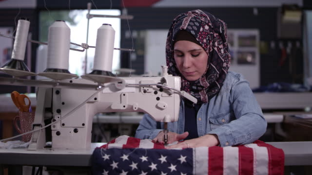 woman wearing headscarf sewing american flag - made in the usa short phrase stock videos & royalty-free footage