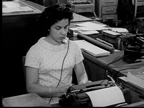 1955 MS woman wearing headset as she types at her desk/ Buffalo, New York
