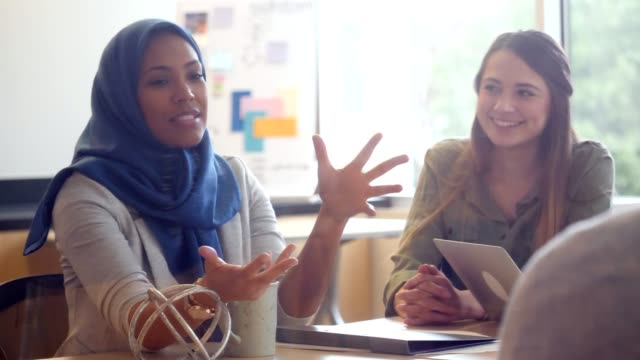 woman wearing hijab gestures as she shares her ideas with her creative group - headscarf stock videos & royalty-free footage