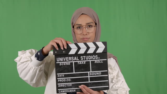 woman wearing hijab holding cinema clacket on chroma - modest clothing stock videos & royalty-free footage