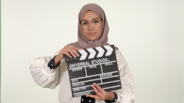 woman wearing hijab holding cinema clacket - modest clothing stock videos & royalty-free footage