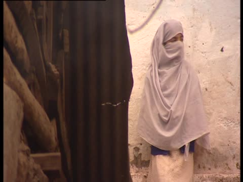woman wearing hijab leans against wall in the street - 僧衣点の映像素材/bロール