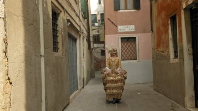 woman wearing historical clothing and carnival mask adjusting headdress and walking in narrow alley - historical clothing stock videos & royalty-free footage