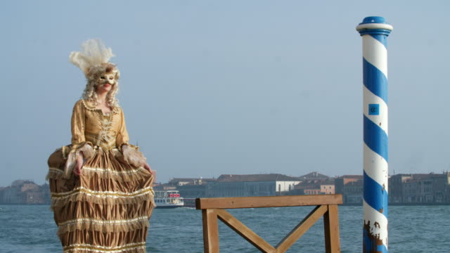 woman wearing historical clothing and carnival mask by canal, san giorgio maggiore church in background - historical clothing stock videos & royalty-free footage