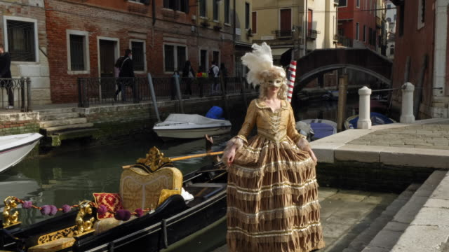 woman wearing historical clothing and carnival mask by canal - historical clothing stock videos & royalty-free footage